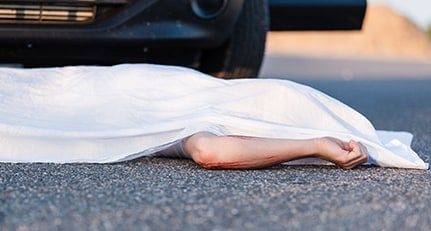 body covered by a sheet lying on the street