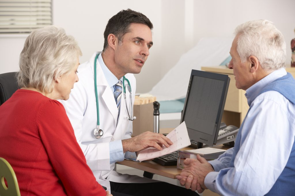 A senior couple having a consultation with a doctor at a desk.