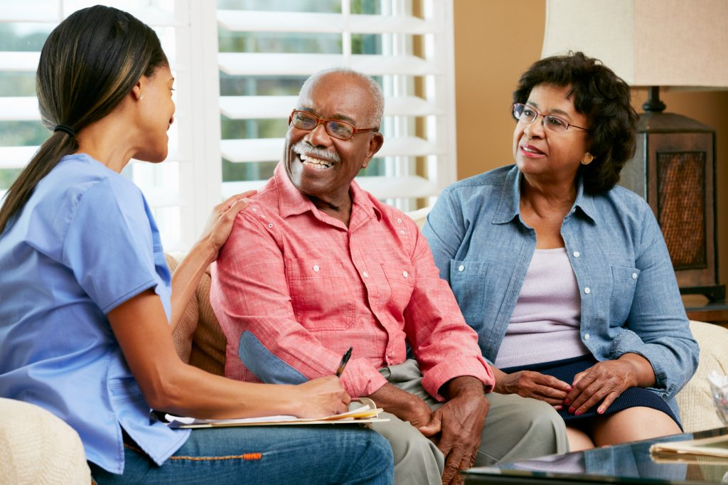 A senior couple sitting on a couch in their home, talking with a nurse in blue scrubs who is taking notes during a visit.