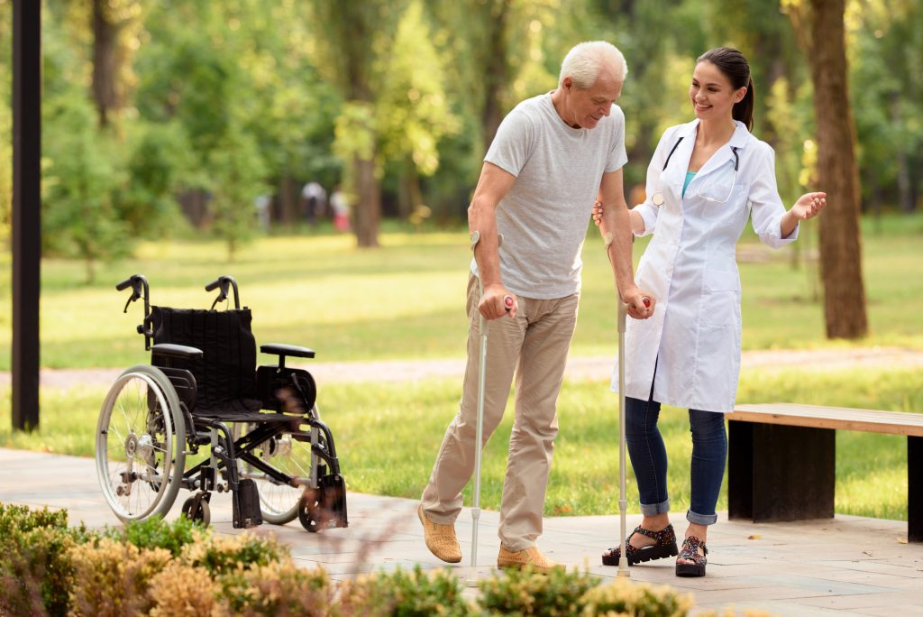 A doctor aids a white-haired senior individual walking on crutches in a park outside, with a wheelchair parked a few steps behind them.