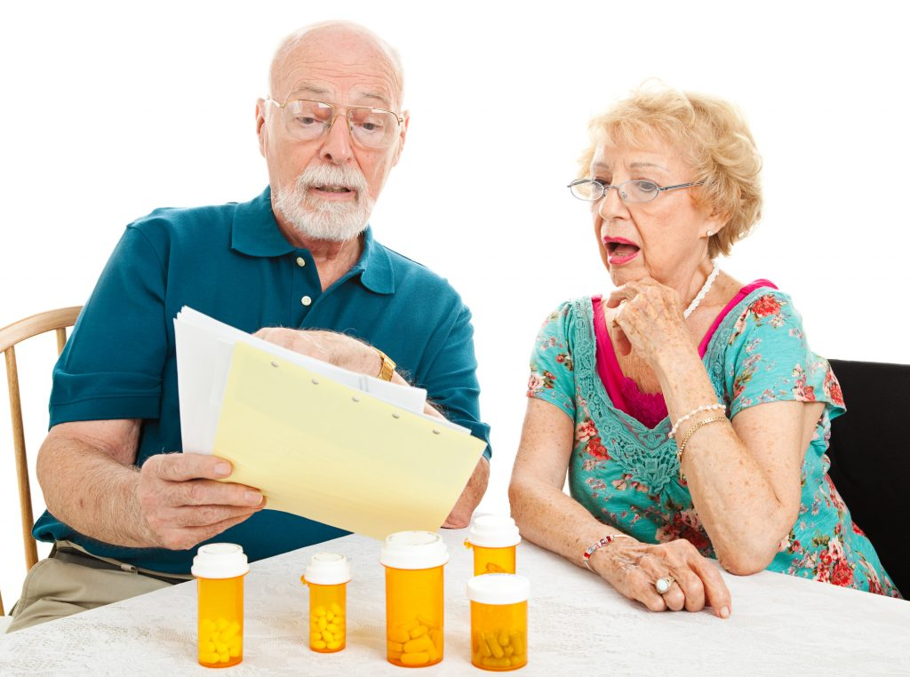 A senior couple sitting at a table with various bottles of prescriptions arrayed on top of it, while they review a stack of paper medical bills.