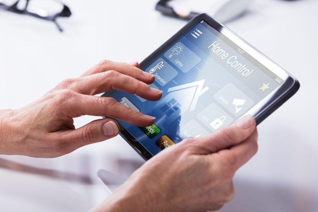 Close-up view of a person's hands holding a tablet, the screen of which displays a smart home control hub with icons for controlling lighting, temperature, security, and locks.