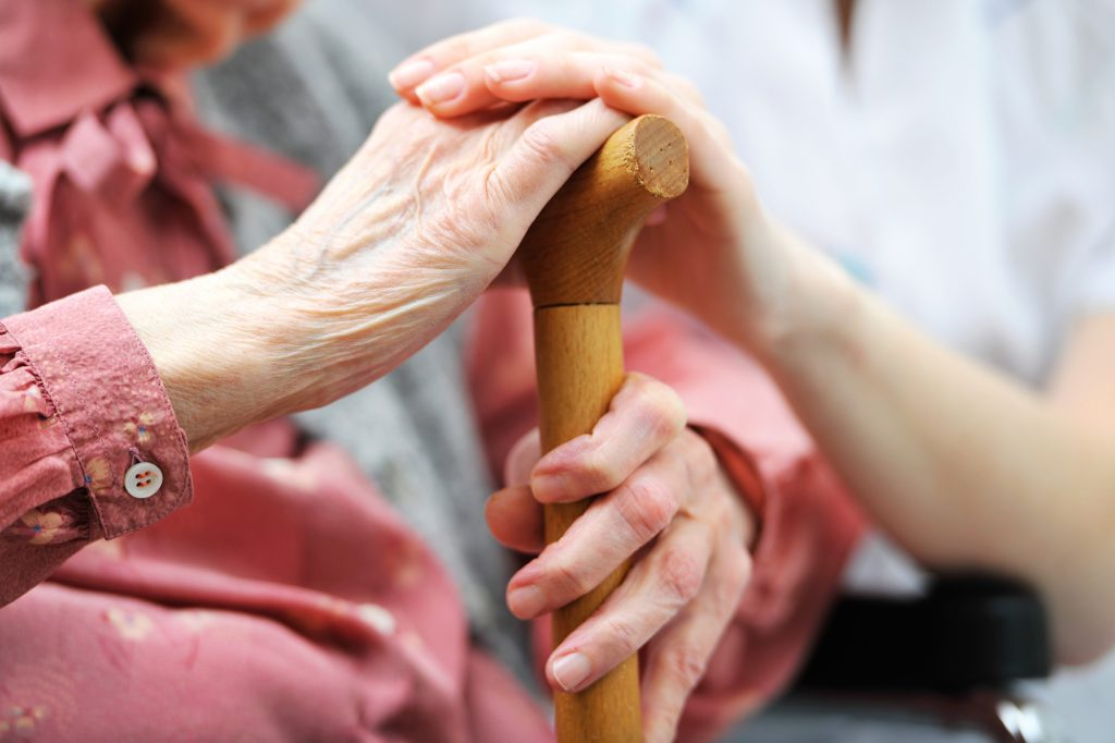 Close-up of a senior individual's hand holding a wooden cane, with a younger person's hand resting on top of the senior's hand.