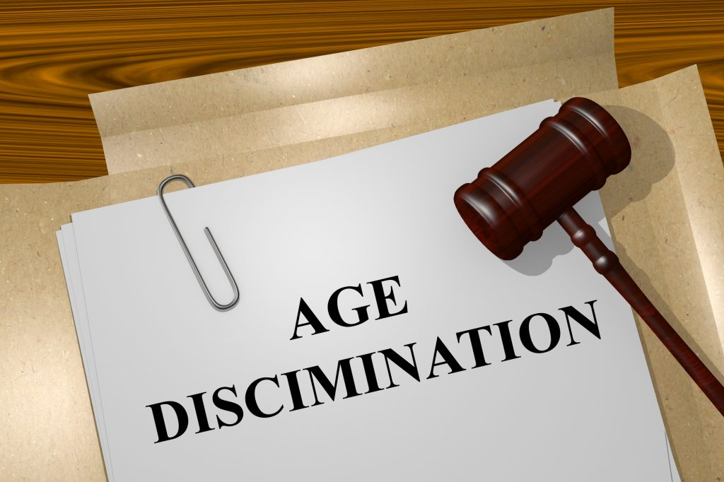 "A wooden gavel resting atop a folder of papers reading ""Age Discrimination."""