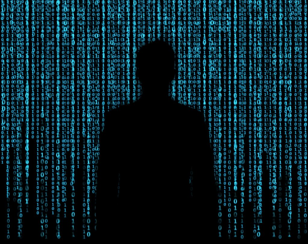 A shadowy human figure silhouetted by cascading green lines of computer code.