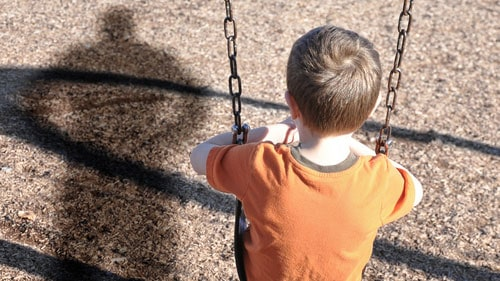 Adult Standing Behind Boy Sitting On Swing Depressed