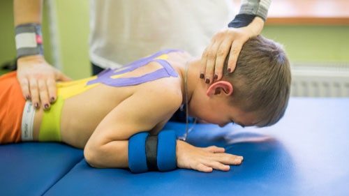 Physical Therapist Working With Cerebral Palsy Boy