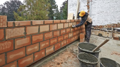 Bricklayer Worker Building New Block And Mortar Wall