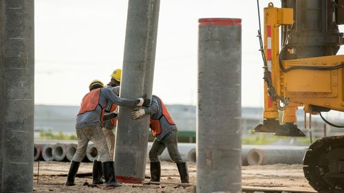 Commercial Construction Site Workers Installing Precast Concrete Piles