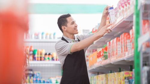 Grocery Store Worker Arranging Beverages Refrigerated Display Shelf
