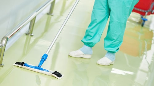 Hospital Worker Washing Floor Using Disinfecting Chemicals