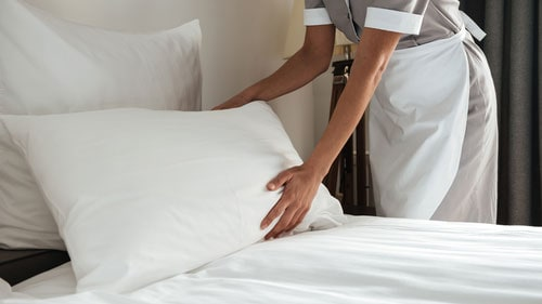 Hotel Worker Changing Bed Sheets