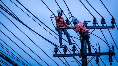Linemen Power Workers Installing High Voltage Power Line