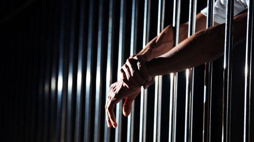 Incarcerated Man Hands Through Jail Cell