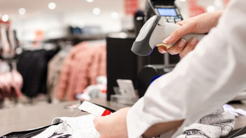 Female Retail Employee Scanning Clothing Price Tag