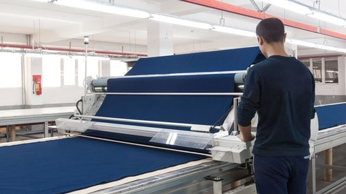 Textile Mill Worker Controlling Fabric Equipment